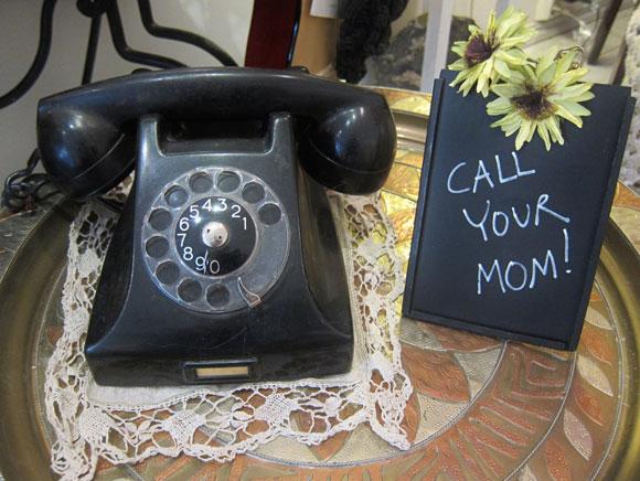 vanha puhelin ja call your mum kirjoitettuna liitutaudulle